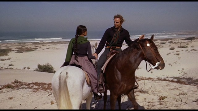 Parting on the Beach - Man on brown horse, woman on white horse shake hands on the beach