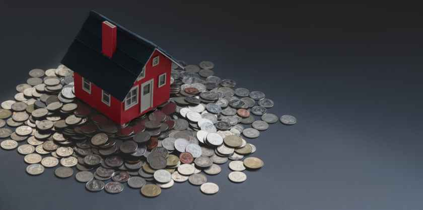 carton miniature house placed on table with stack of coins