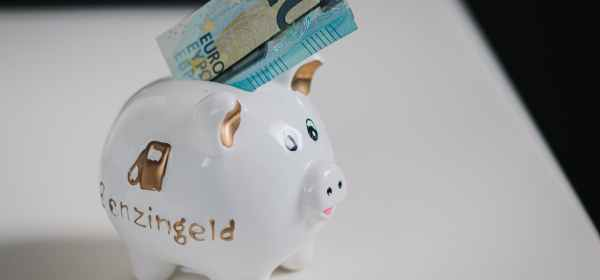 pink ceramic piggy bank with banknotes