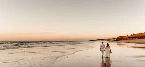 couple in wedding wear walking along seashore