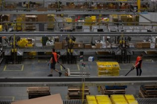Employees pull carts containing online orders at the Amazon.com Inc. fulfillment center in Robbinsville, New Jersey, U.S., on Thursday, June 7, 2018. Seattle-based Amazon hasn't yet announced the exact date for this year's Amazon Prime Day, the e-commerce giant's big July sales promotion. Photographer: Bess Adler/Bloomberg