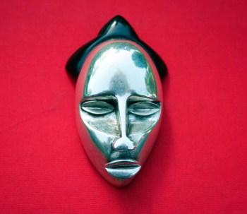 Masque africain en argent, fonte à la cire perdue, yeux rapportés et coiffe en corne