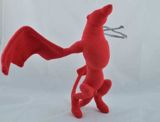 An unfinished crocheted dragon/wyvern in red.