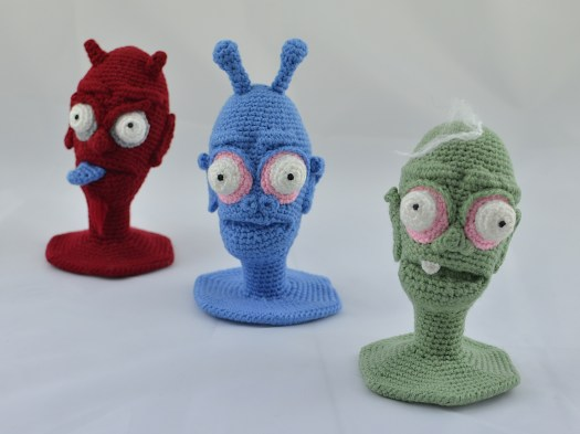 Three crocheted heads arranged diagonally across a white background. At the back is a red demon. In the middle, a blue alien. At the front, a green zombie.