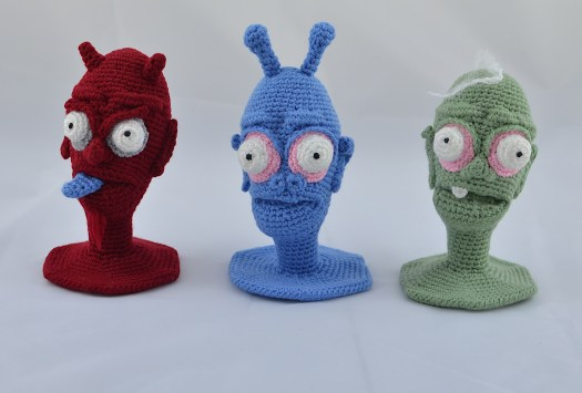 Three crocheted heads sitting in a straight line. To the left, a red demon. In the middle, a blue alien. To the right, a green zombie.