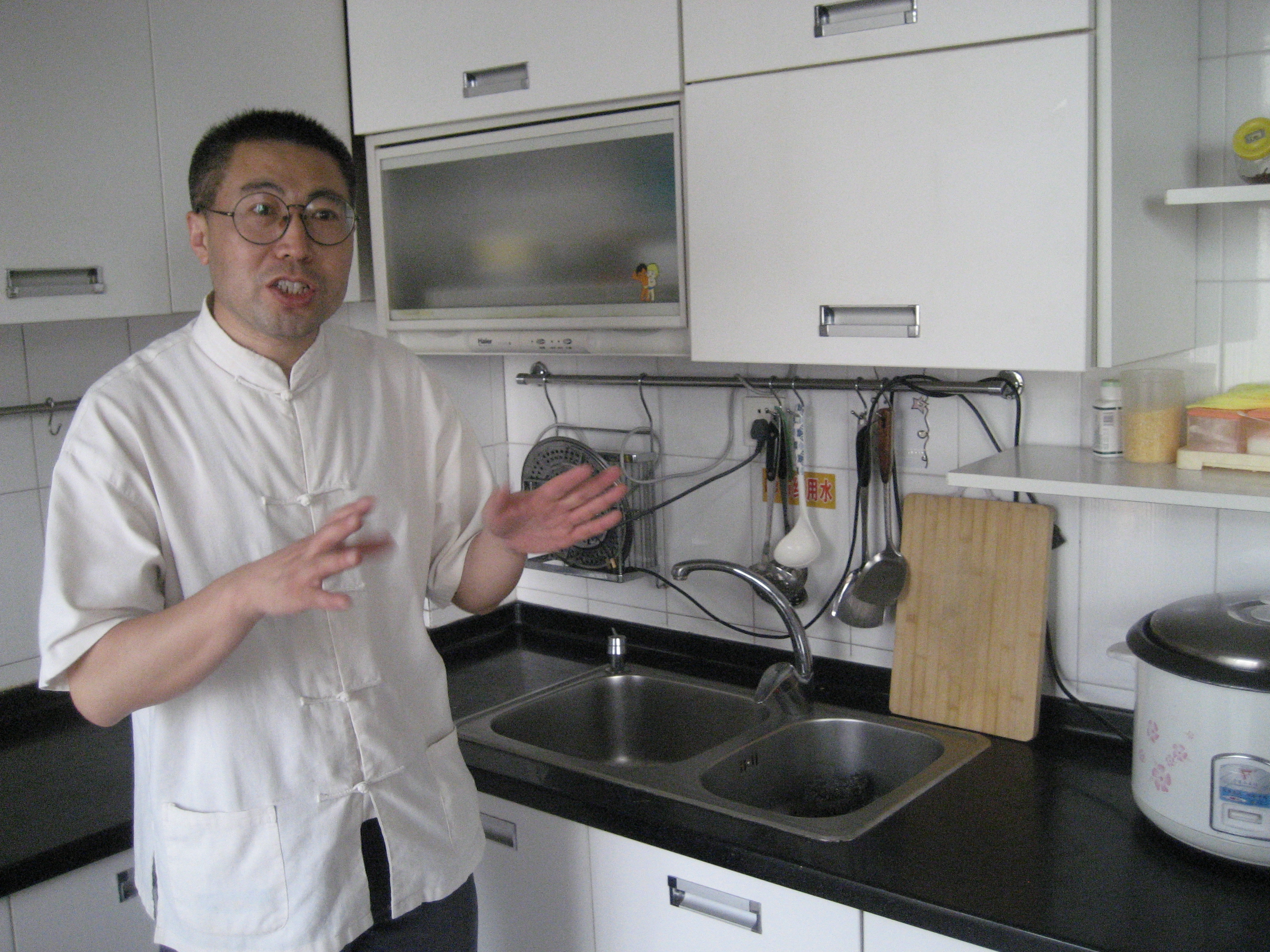 """Huang He shows off the model """"kitchen"""" where migrant trainees learn how to cook."""