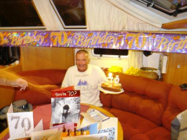 Lawrence surrounded on his 70th birthday with tinsel, cake, candles, prezzies and cards