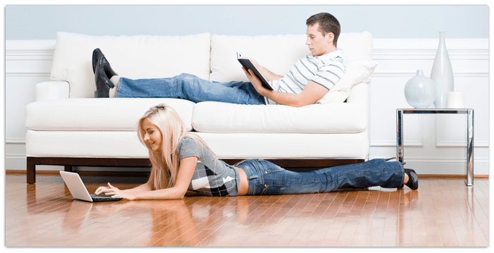 Man and woman can read peacefully thanks to acoustic flooring underlayment by Synergy
