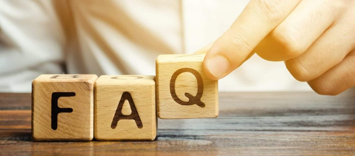 Businessman puts wooden blocks with the word FAQ (frequently asked questions). Collection of frequently asked questions on any topic and answers to them. Instructions and rules on Internet sites