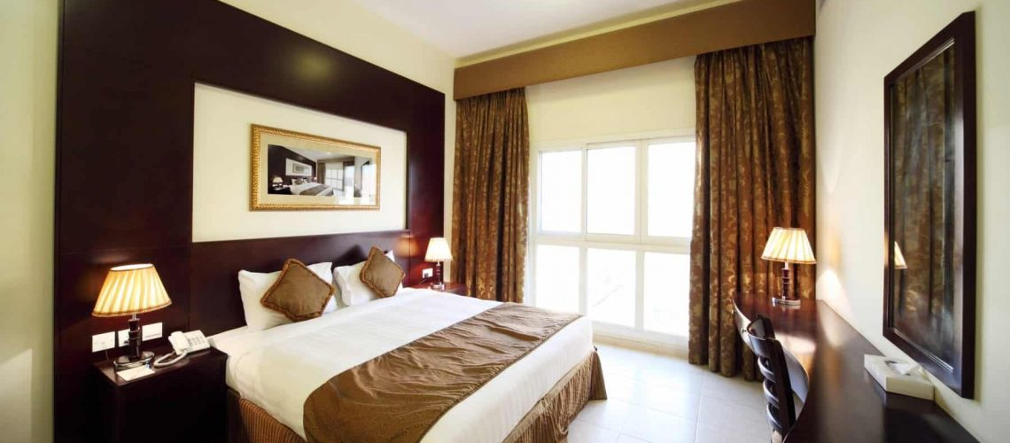 bedroom with white walls opened curtain big double bed general view