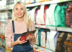 Young woman selecting animal food in pet shop