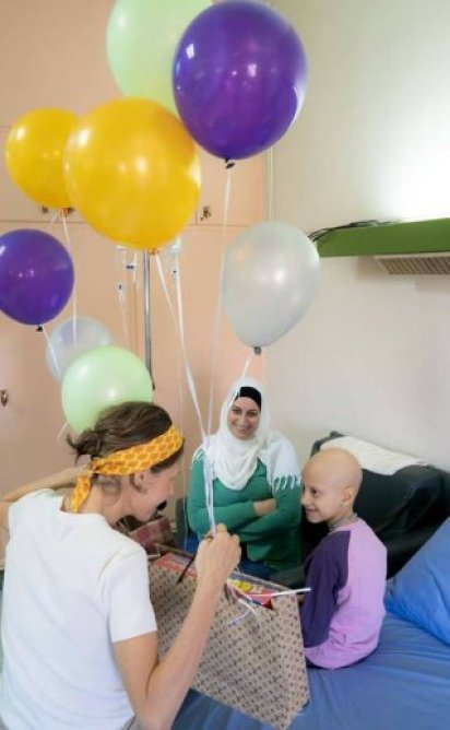 Mrs. Asma-a Al-Assad brings balloons to children being treated for cancer.