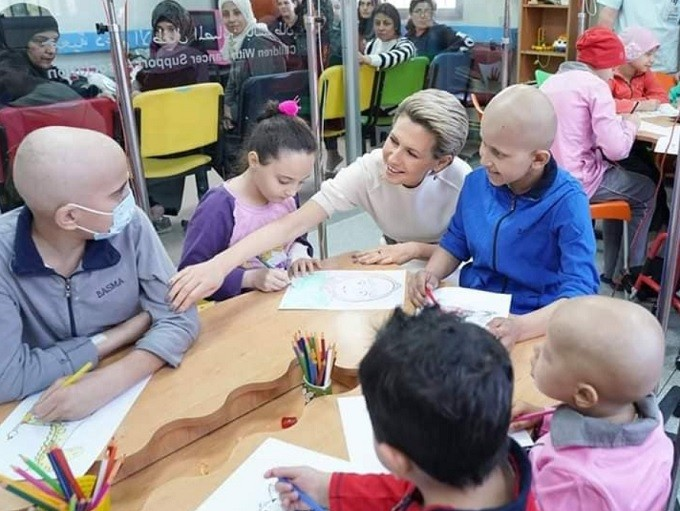 First Lady Asmaa Assad with children receiving treatment from cancer at al-Biruni University Hospital