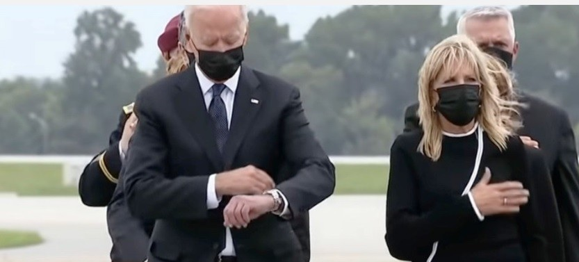 Demented Joe checks his watch at the somber occasion of Americian troops killed by terrorists coming home in caskets.