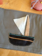 Båten er laget med en enkel applikasjonsteknikk - delene er sydd på med rettsøm og stripene på båten er selve stoffet