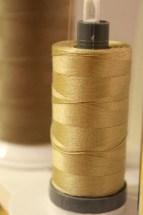 Aurifils tråd skimrer i gull