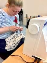 Berit syr sin kjole på symaskinen med en overlocksøm