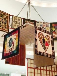 En helt makeløs utstilling - quilter hang i 3 etasjers høyde og tett i tett som perler på en snor