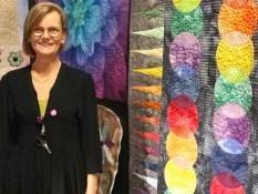 Jill Lindström har magiske fingre - her er hon foran noen av quiltene som er frihåndsquiltet med pepples og fjær