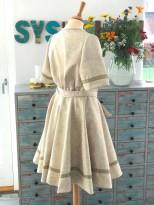 Bakfra sees det tydelig at kjolen har ekstra vidde i livet som holdes inn med knytebåndene som er sydd med i sidesømmen