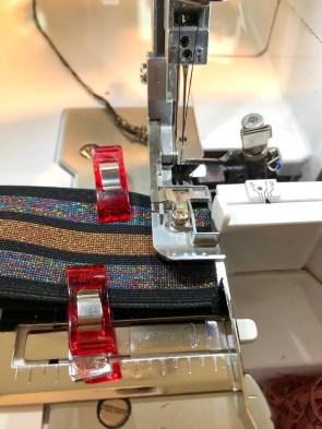 Fest elastikken sammen med wonderclips og sy i kanten av den. Sørg for at det er en lang trådkjede i begge ender av elastikken