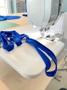 Beltet eller snoren sys enkelt på overlocken. Velg den bredde du vil ha og sy sammen. Sømguiden eller linjalen er også her supergod til å hjelpe deg til å ikke skjære for mye stoff vekk.