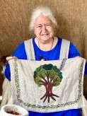 Asta Marie viser frem sitt nydelige Yggdrasil eller Livets Tre som er brodert på hennes forklede