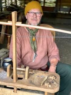 Jeg tror at denne oppfinnsomme mann heter Søren og han har en finurlig maskin til å bore hull i perler som ble brukt til smykker.