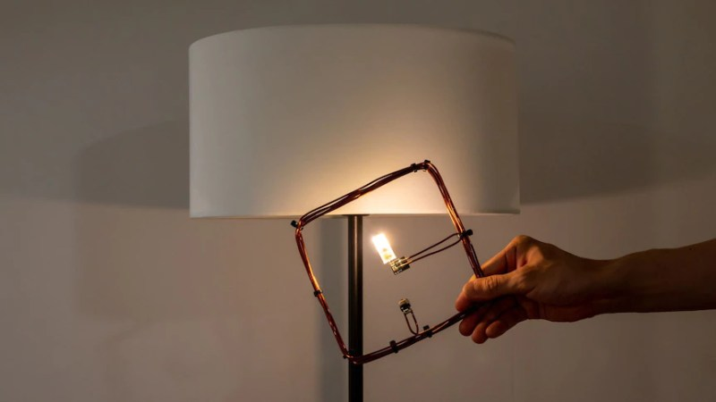 """Room for wireless charging of electronic devices. LED lamp powered by the receiving coil thanks to the magnetic field generated inside the room. Credits: """"Michigan News"""" and The University of Tokyo."""