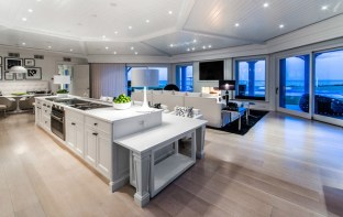Cook's Dream The kitchen basks in the glow of twinkling recessed lighting, and stretches before a wall of windows.