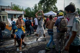 Horgos, 2015. szeptember 16. Egy férfi kõvel a kezében a Horgos-Röszke határátkelõhelynél, ahol migránsok tüntetnek a magyar oldalon álló rohamrendõrökkel szemben, a magyar-szerb határ szerbiai oldalán 2015. szeptember 16-án. A magyar rendõrök könnygázt és vízágyút is bevetettek az õket dobáló illegális bevándorlókkal szemben. MTI Fotó: Sóki Tamás