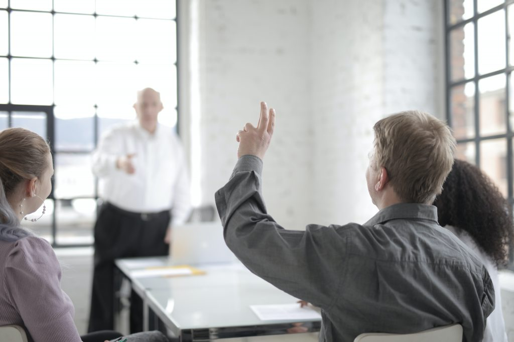 male-employee-raising-hand-for-asking-question-at-conference-3861561