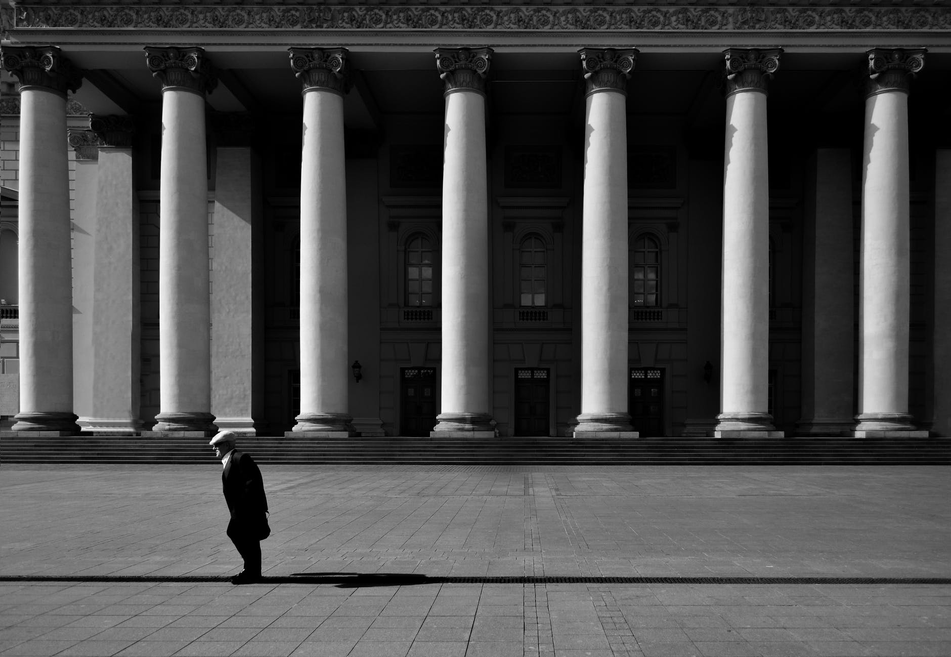 unrecognizable citizen against old urban building with colonnade