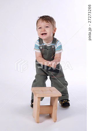 little boy with hammer and wooden chair [27273266