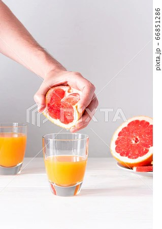 Male hand squeezes grapefruit juice in a glassの写真素材 ...