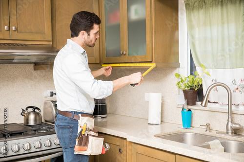 Handyman Measuring A Kitchen Cabinet Buy Photos AP Images