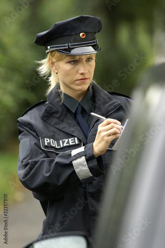 Polizistin schreibt einen Strafzettel Stockfotos und