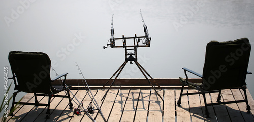 fishing chair crane floor mat for office arm chairs and rods on wooden pier stock photo royalty