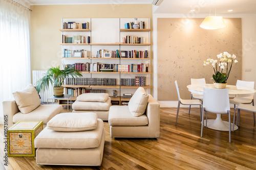 soggiorno in appartamento con tavolo rotondo libreria a muro e parquet curato e pulito in