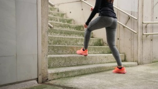 Step up exercise on urban stairs. Woman training hiit outside. Female athlete doing knee raises workout.