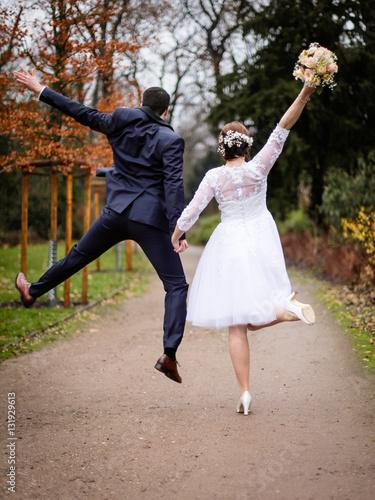 Ehepaar Brautpaar von hinten springt auf einem Weg mit