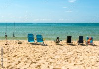 """""""Row of empty beach chairs and fishing poles on the beach ..."""