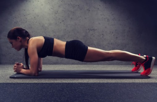 woman doing plank exercise on mat in gym