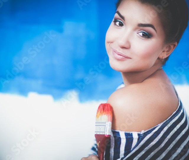 Beautiful Young Woman Doing Wall Painting Standing On Ladder Beautiful Young Woman