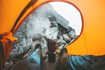 (can you use a camping stove inside a tent) Man using a backpacking stoves around the tent's vestibule