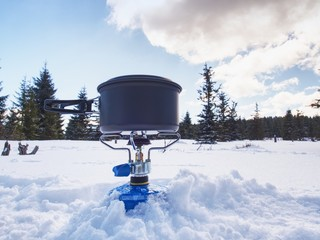 backpacking stove in winter, canister fuel covered with snow
