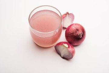 Onion juice in a glass with raw onions.