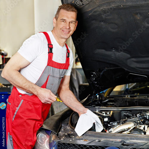 Car mechanic changes the oil of the engine