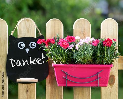 Gartenzaun mit Blumen und DankeSchild Stockfotos und