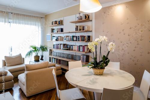 soggiorno in appartamento con tavolo rotondo libreria a muro e tappezzeria con motivo di